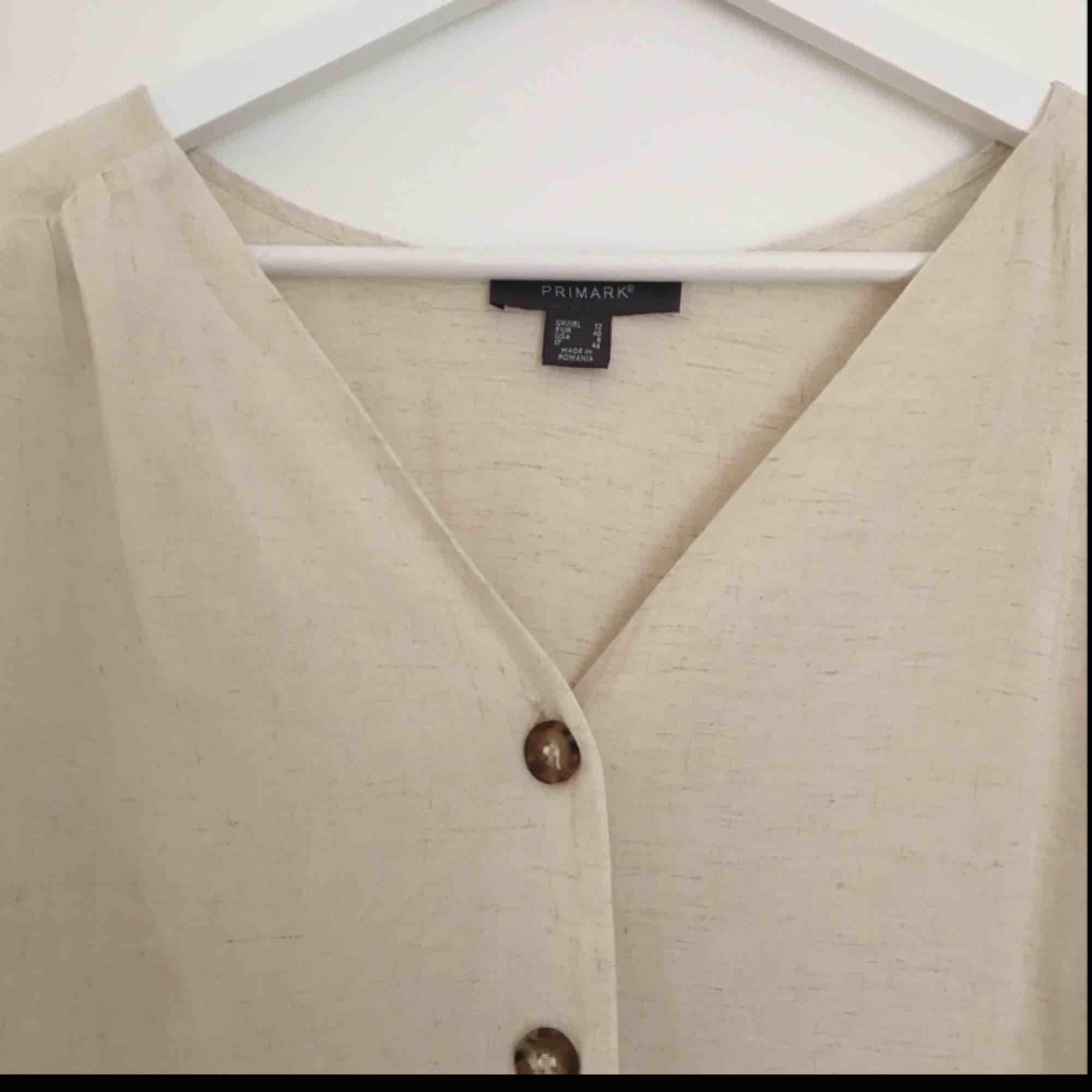 Somrig blus i vit/beiche med bruna knappar från Primark i London. Aldrig använd endast provad hemma! Frakt tillkommer men kan också mötas upp i Stockholm! 🍇🌿🍋. Blusar.