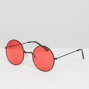 Ett par runda 90-tals glasögon med rött glas.