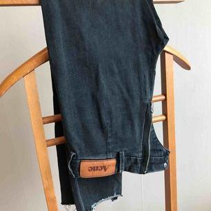Avklippta Jeans från Acne i storlek 26/32 Hål över knäna och dragkedja baktill