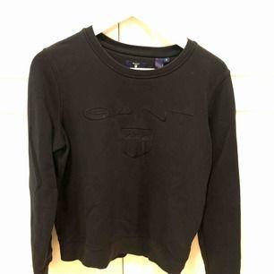 Svart Gant tröja med svart tryck, nypris 999kr, använd 3 gånger. Frakten står köparen för, annars möts upp i Uppsala