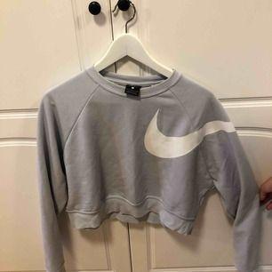 Croppad sweatshirt från Nike, ljusblå med vitt tryck, använd 3 gånger. Fint skick. Frakten står köparen för, annars möts i Uppsala