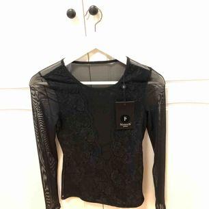 Långärmad tröja från sisterS, mesh med v-ringad spets i fram. Aldrig använd med prislapp kvar.  Frakt står köparen för, annars möts i Uppsala