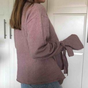 Stickad overaller tröja med knytband runt ärmarna