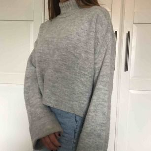 Stickad grå tröja.