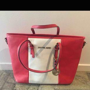 Vit och röd randig Michael Kors väska i relativt bra skick. OBS, trasig dragkedja på facket på backsidan av väskan. Köptes för: 500kr