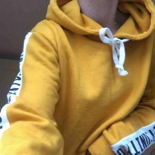 Fin croppad hoodie från bikbok i en tuff gul färg men unity i svart vitt skrivet på båda armarna