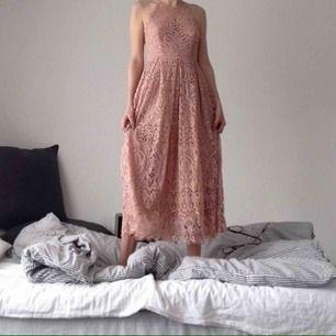 Ljusrosa spetsklänning med halterneck o lätt utställd kjol. Jag är 163 cm, klänningen mäter till halva smalbenet. superdrömmig o perfekt för fest, bröllop, you name it!  Aldrig använd. Nypris 800kr.   Kan mötas upp i tallkrogen eller centralt i sthlm.