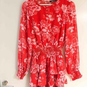 Snygg röd klänning med vita blommor från Gina Tricot. Använd ett fåtal gånger. Storlek 36. Köparen står för frakt.