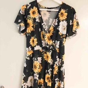 Snygg svart klänning med solrosor från Gina Tricot. Storlek M. Använd ett fåtal gånger. Köparen står för frakt.