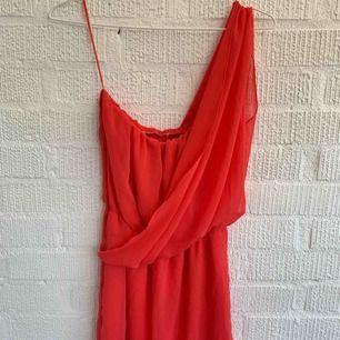 Klänning i persiko färg.  Bilden visar mer röd än vad den är.  Utan band och en tunn arm som man drar över axeln.