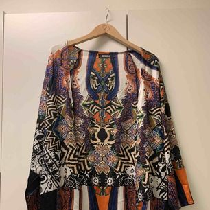 Mönstrad kimono från Missguided. Perfekt för festivaler! Härligt silkeslen. Aldrig använd tyvärr, så den är precis som ny! Säljs pga används inte. Jag är suuuuperkort (därför ser den väldigt lång ut)  Möts i Falun, annars tillkommer frakt.