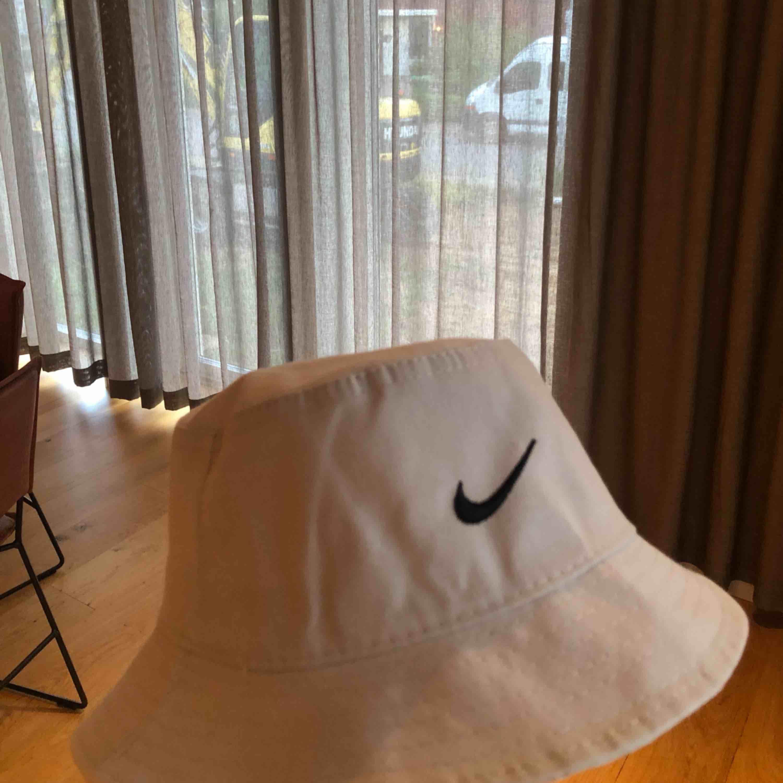 En !fake! Nike bucket hat i färgen ljusgrå. Endast testad en gång. Frakten ingår i priset 💕 xoxo (sista bilden är ej min!) . Accessoarer.