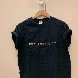 """Svart tisha med tryck """"New York"""" - från New York! Avklippt nertill. Känns mer som XS.  Möts i Falun, annars tillkommer frakt."""