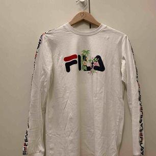 Vit FILA tröja med härliga detaljer. Använd 2 gånger, så den är i nyskick! Förtjänar mer uppmärksamhet och ska därför säljas vidare. Passar XS-S beroende på hur man vill att den sitter!  Möts i Falun, annars tillkommer frakt :)