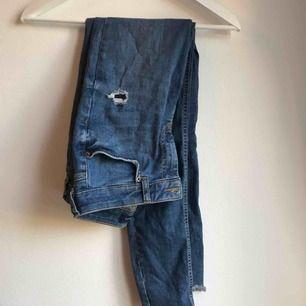 Snygga jeans i perfekt färg med slitningar. Avklippta längst ner.