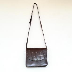 Mörkrun vintage vegan-leather snakeskin väska. Bandet går att justera ganska mycket så den blir längre och kortare. I fint skick! Frakt 59 kr.