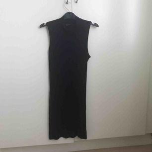 Tight svart ribbad klänning som går upp lite vid halsen.
