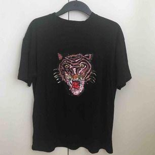 T-shirt med glittrigt tryck av en tiger. Oversize i storlek på någon som är XS/S