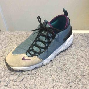 Nike Air Footscape storlek 41. Inga defekter förutom allmänt slitage under sulan såklart. Sparsamt använda så i bra skicka. Nypris 1399