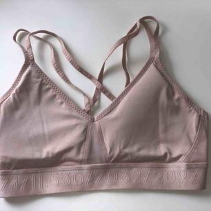 """Sport-bh från H&M. Den är ljusrosa och jättefin på. Genomskinligt tyg """"i klyftan"""" och likadant i ryggen.  Aldrig använd pga för liten."""