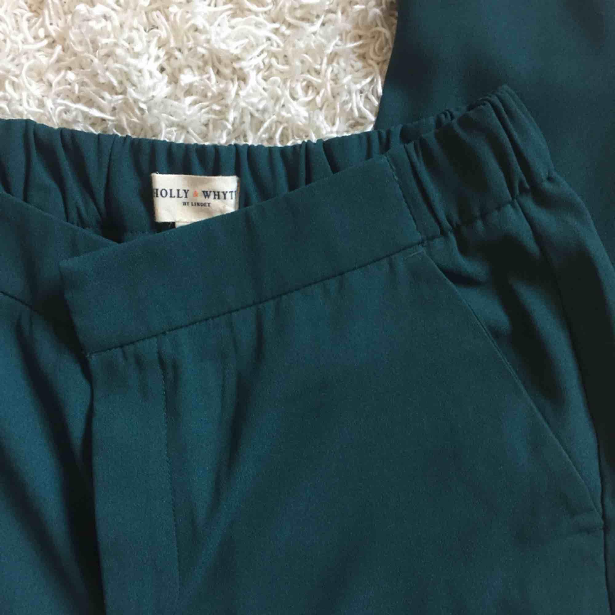 Skitsnygga gröna byxor från Holly & Whyte. Aldrig använda! Perfekta kombon av kostymbyxor och mjukisar, så passar allt från att ha till kontoret eller en sväng på stan. Resår i midjan för bekväm passform 🤩  📬 Frakt 54 kr. Jeans & Byxor.