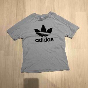 En ljus/baby blå t-shirt med ribbat tyg en del av armenfrån adidas Använd 2 gånger och i bra skick    Ni står för frakt