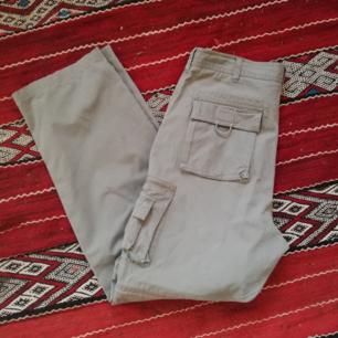 Grå/beige vintage cargobyxor i stl L (se mått). Ganska rymliga och supersköna! Fullt av fickor, och avtagbara ben som går att göra om till shorts. Midjemått 88 cm och innerbenslängd  81 cm. Frakt 59 kr.