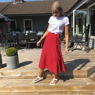 Kjol i röd färg från Indiskan, använd fåtal gånger, kjolen har ett litet hål vid sidan men inget som syns när kjolen är knyten, bra kvalité