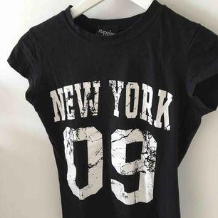 Svart T-shirt med New York tryckt i vitt på framsidan