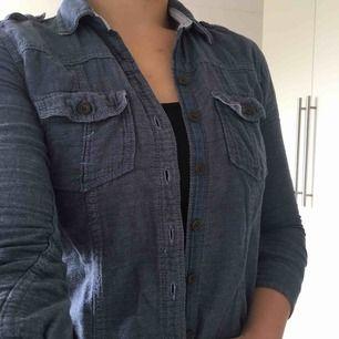 Fin och skön bomullsskjorta från Abercrombie&Fitch. Skjortan är i jeansfärgat tyg med ljusblå/vitrandigt innertyg och i mycket bra skick!
