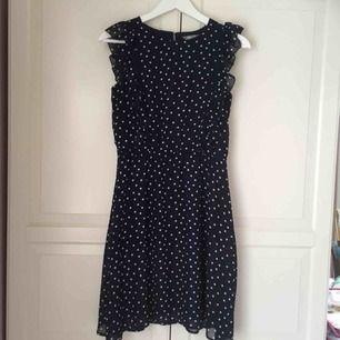 Prickig mörkblå klänning med volanger från Kappahl. Storlek 170, passar mig som har 36. Aldrig använd, mycket fint skick!