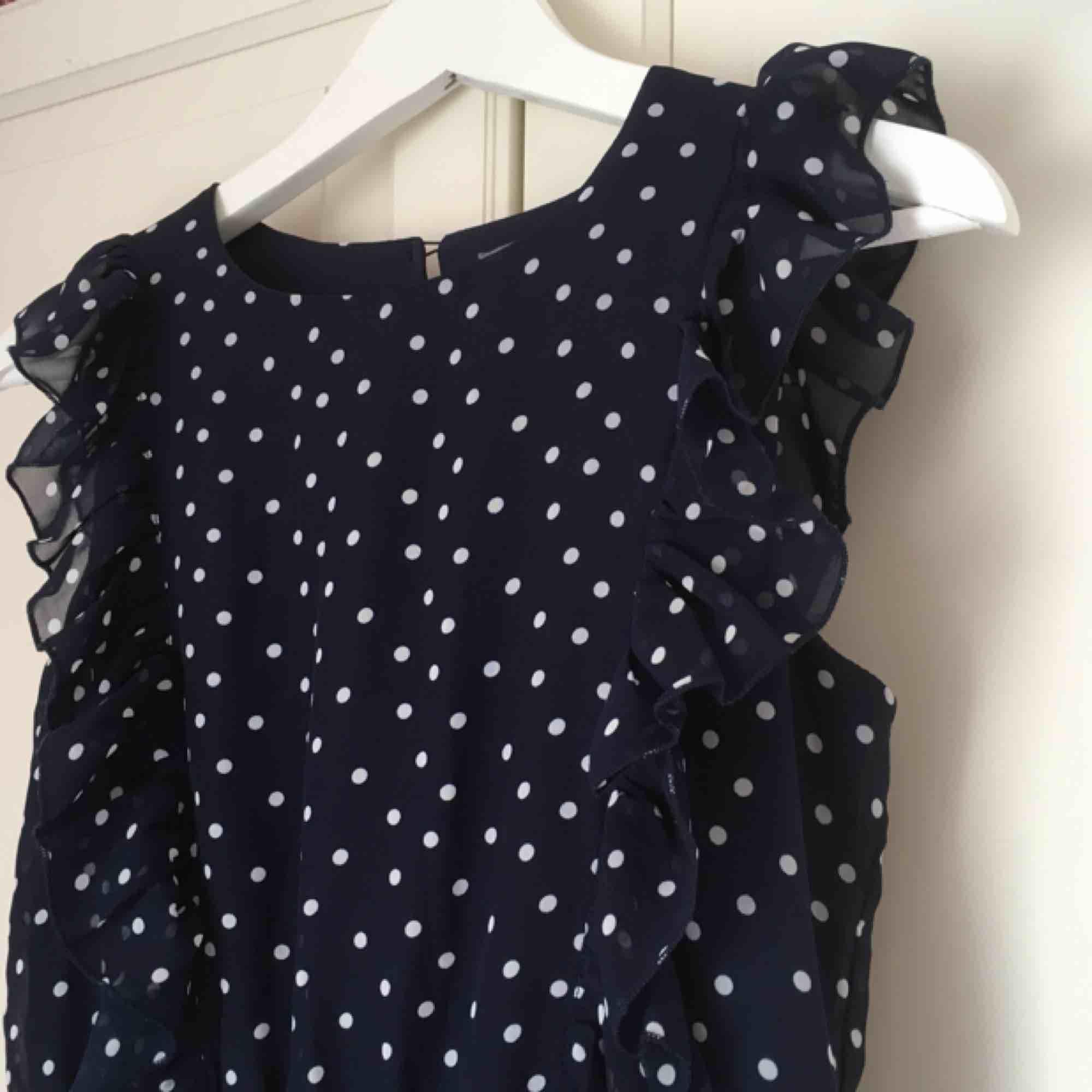Prickig mörkblå klänning med volanger från Kappahl. Storlek 170, passar mig som har 36. Aldrig använd, mycket fint skick!. Klänningar.