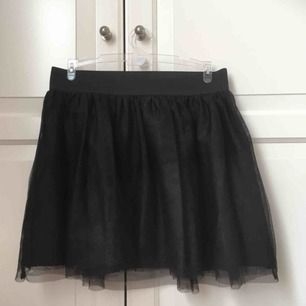 Svart tyllkjol från H&M. Fungerar bra som underkjol även om den är i barnstorlek. Relativt bra skick, väl använd.