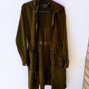 Oversized oanvänd kappa i olivgrön färg. Kappan har luva och fickor. Finns även dragsko i midjan för att framhäva kurvorna om man föredrar det