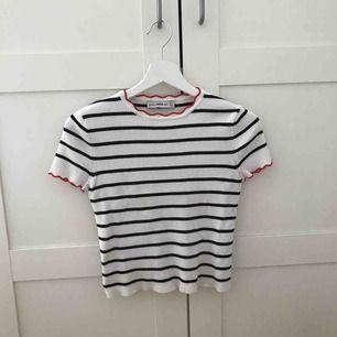 """Svart och vitrandig T-shirt med röda detaljer. Både ändarna på ärmarna och kragen är lite """"vågiga"""" (se bild på kragen). Endast använd en gång. Jättefint skick."""