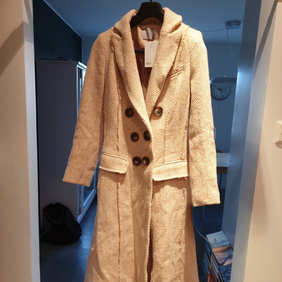 Figursydd kappa från Asos. Oanvänd med lapp kvar. 23%ull. Kommer med en extraknapp. Vit och blek orange. Jackor.