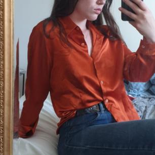 Skjorta i fantastisk orange färg. Lätt figursydd. Storleken är en Italiensk 46