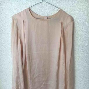 Silkesblus från Velour. Ljusrosa/beige med silvriga knappar i ryggen.