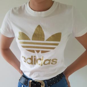 En vit adidas t-shist med guldfärgad logga på framsidan. Är storlek 36 men skulle säga att den passar bättre på en 34 då den är liten i modellen. Använd endast 1 gång då det inte är min stil. Köparen står för frakten!🌻