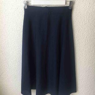 A-linje kjol i mörkblått som är väldigt snäv i midjan. 50-tal