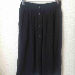 Midi kjol från Monki med knappar och två fickor. Resår i midjan