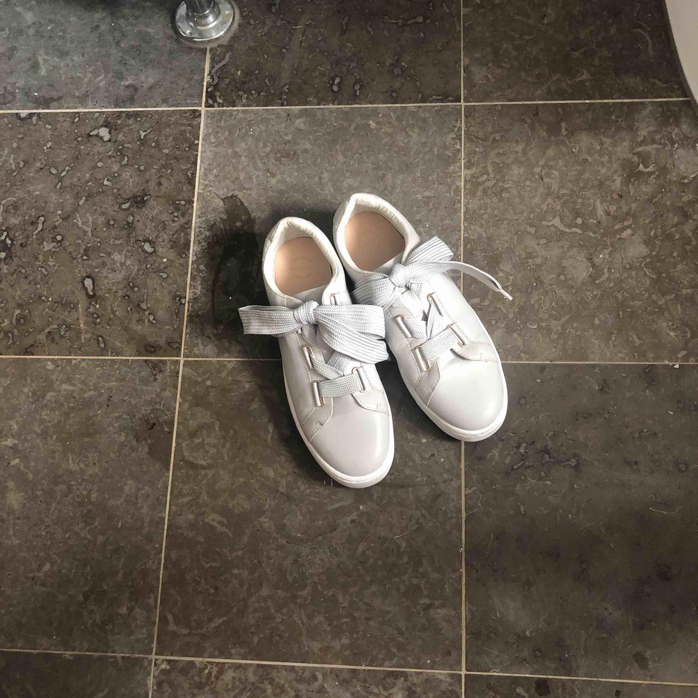 Säljer ett par gråa super coola sneakers ifrån Pull and bear. Dem har endast kommit till användning 1 gång och är därför som nya. Är i storlek 40 men funkar även på mih som har 39. Skorna har bred grå snörning som enligt mig gör hela skon unik! . Skor.