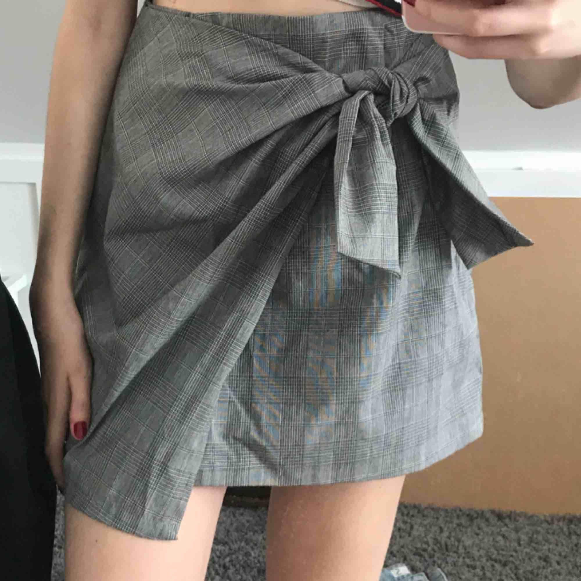 Söt kjol med knytning där fram och plaid mönster. Går att justera knytningen. Nyskick!. Kjolar.