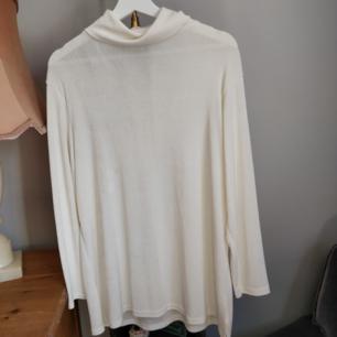 Polotröja i glansigt vitt tyg. Köpt på secondhand i Malmö.