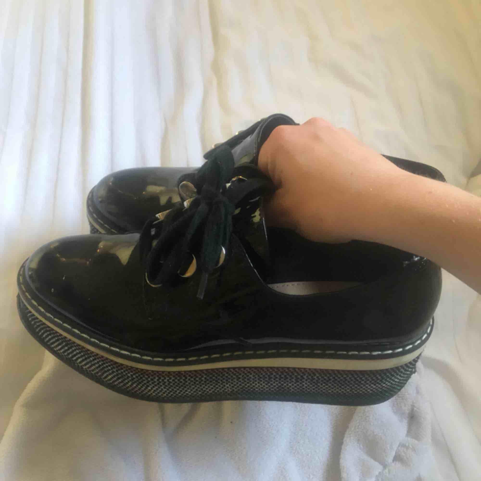 Svinsnygga platå-kängor, i svart lack med färgdetaljer på klacken. Köpta i Singapore för ett år sedan men kommer sällan till användning länge. fint skick, endast skosnören skulle behövas bytas ut. Skor.
