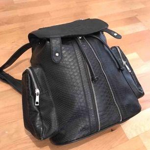 """Svart, rymlig och riktigt snygg ryggsäck från topshop. Går att stänga med knappar och/eller ett """"band"""".  Säljes pga den inte används längre🌸 Nypris ca 400kr Frakt betalas av köparen!"""