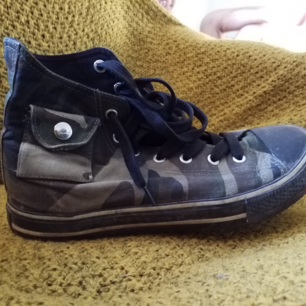 Militärmönstrade skor i conversemodell med fickor. Litet hål på ytan bak på ena skon, syns på sista bilden