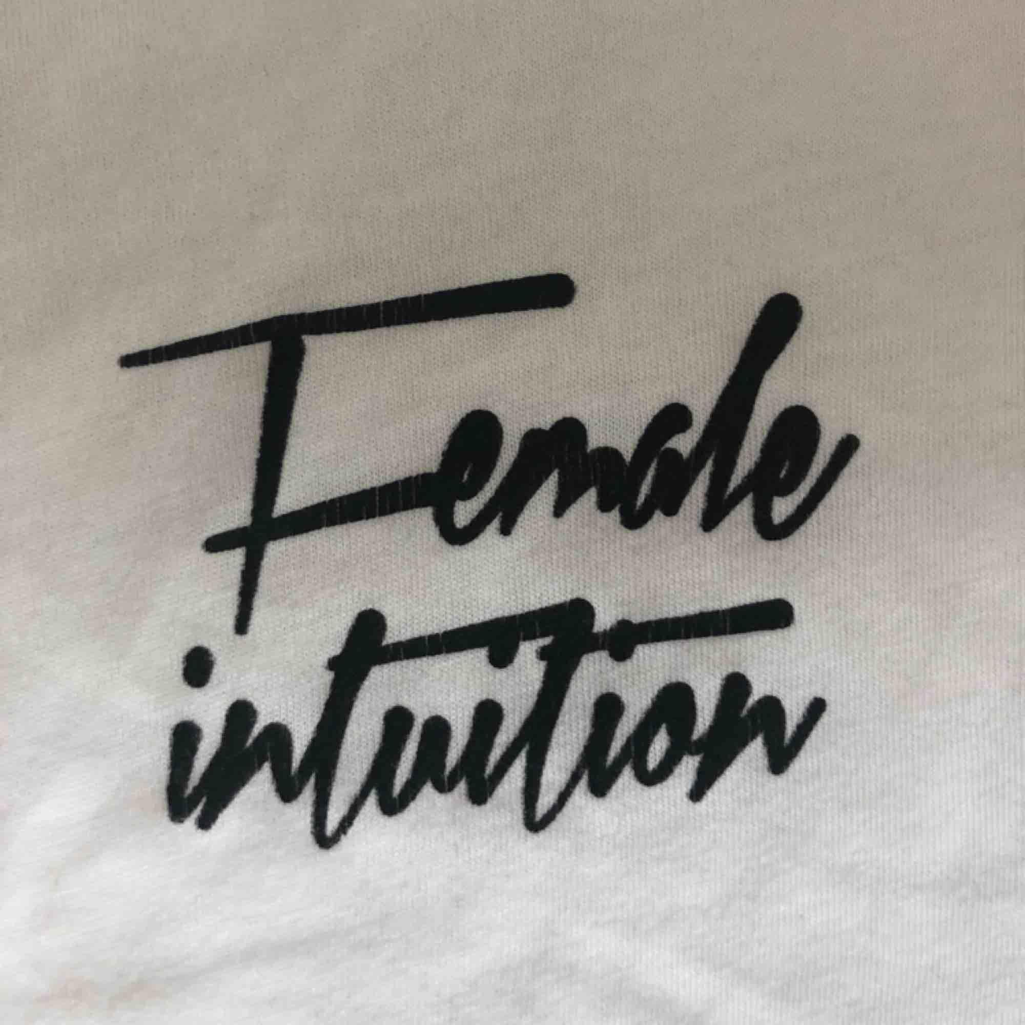 """Vit t-shirt med texten """"Female intuition"""" på bröstet. Väl använd vilket visar sig genom minimala sprickor i trycket (bild 3) men syns knappt! Fri frakt💖💖. T-shirts."""