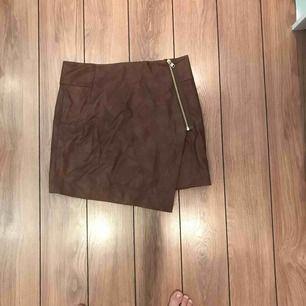 En kjol i brunt läder i storlek 38 med en guldig dragkedja