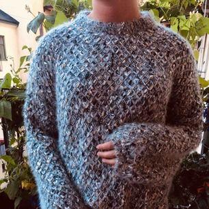 Fin stickad tröja med ballongärm, virkad i blå/grå/guldglitter.